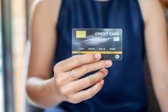 Jeune femme occasionnelle d'affaires tenant la carte de crédit pour des achats en ligne tout en faisant des ordres dans le café a photo libre de droits