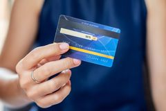 Jeune femme occasionnelle d'affaires tenant la carte de crédit pour des achats en ligne tout en faisant des ordres dans le café a photographie stock