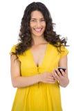 Jeune femme occasionnelle de sourire envoyant le message textuel Photos stock