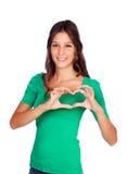 Jeune femme occasionnelle faisant un coeur avec ses mains Photographie stock libre de droits