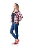 Jeune femme occasionnelle heureuse dans les espadrilles rouges et blanches et des jeans recherchant souriants Image stock