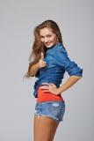 Jeune femme occasionnelle heureuse se dirigeant à vous, sur le fond gris Image stock