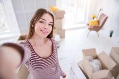 Jeune femme optimiste prenant le selfie dans la nouvelle maison Image libre de droits