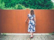 Jeune femme ouvrant la porte orange Photos libres de droits