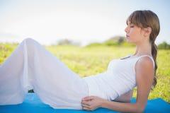 Jeune femme paisible détendant sur son tapis Photo libre de droits