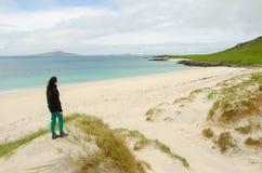 Jeune femme par derrière admirant une plage blanche vide de sable Photographie stock