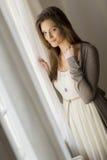 Jeune femme par la fenêtre photographie stock