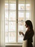 Jeune femme par la fenêtre images libres de droits