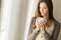 Jeune femme par la fenêtre photos stock
