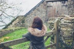 Jeune femme par la porte en dehors de la grange Images libres de droits
