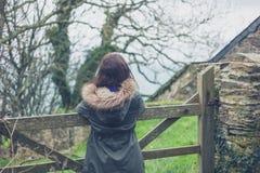 Jeune femme par la porte en dehors de la grange Photographie stock