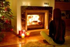 Jeune femme par une cheminée sur Noël Photo stock