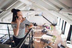 Jeune femme parlant au téléphone avec un ami et souriant tout en regardant loin Café brouillé, grandes fenêtres à un arrière-plan Images stock