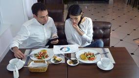 Jeune femme parlant au téléphone pendant le déjeuner et demandant à son associé masculin l'aide Image libre de droits