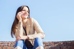 Jeune femme parlant au téléphone portable Photographie stock libre de droits