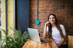 Jeune femme parlant au téléphone portable et à l'aide de l'ordinateur portable dans la boutique de café Photos libres de droits