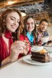 Jeune femme parlant au téléphone portable tout en appréciant une tasse de café Photographie stock
