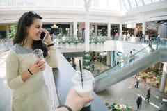 Jeune femme parlant au téléphone tandis que mail de marche Photographie stock libre de droits