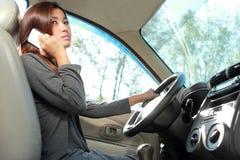 Jeune femme parlant au téléphone tout en conduisant Images libres de droits