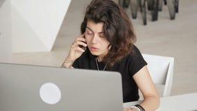 Jeune femme parlant au téléphone tout en se reposant dans le bureau à l'intérieur clips vidéos