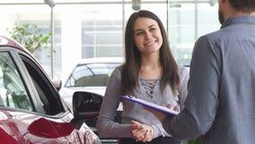 Jeune femme parlant au vendeur au concessionnaire automobile photographie stock libre de droits