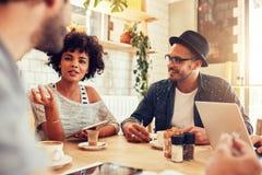 Jeune femme parlant avec des amis à un café Photographie stock