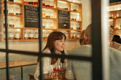 Jeune femme parlant avec des amis au-dessus des boissons dans une barre Photo stock