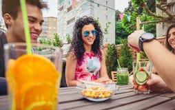 Jeune femme parlant avec des amis dans un jour d'été Image stock