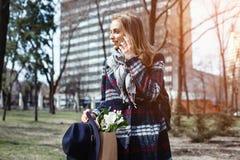 Jeune femme parlant avec l'ami au téléphone de cellules marchant un jour ensoleillé en parc Belle fille dans un manteau, chapeau Photographie stock