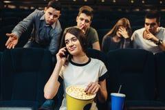 Jeune femme parlant par le téléphone dans le cinéma Images stock