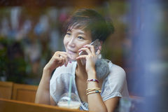 Jeune femme parlant sur le smartphone dans le café Image stock