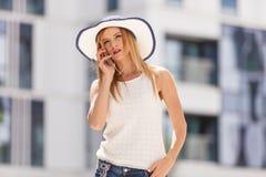 Jeune femme parlant sur le smartphone dehors Image libre de droits