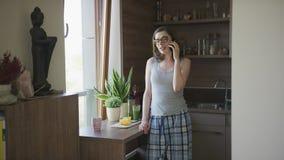 Jeune femme parlant sur le smartphone se tenant dans la cuisine banque de vidéos