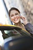Jeune femme parlant sur le téléphone portable en le taxi jaune image libre de droits