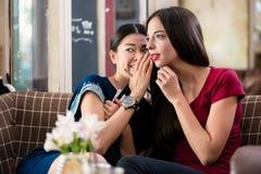 Jeune femme partageant des secrets avec son meilleur ami Photo stock