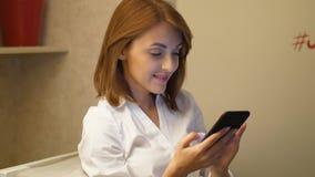 Jeune femme passant en revue dans le smartphone et souriant heureusement banque de vidéos