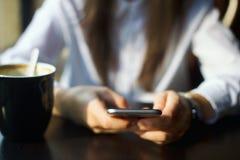 Jeune femme passant en revue sa fin de smartphone  Image libre de droits