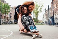 Jeune femme patinant ensemble sur un longboard Photographie stock libre de droits