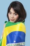 Jeune femme patriote enveloppée dans le drapeau brésilien au-dessus du fond bleu Photo stock