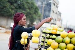 Jeune femme payant des fruits au marché en plein air Photos stock