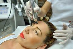 Jeune femme pendant la demande de règlement cosmétique Photos stock