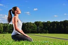 Jeune femme pendant la méditation de yoga en parc image stock