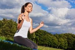 Jeune femme pendant la méditation de yoga en parc images libres de droits