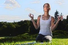 Jeune femme pendant la méditation de yoga en parc photo libre de droits