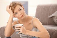 Jeune femme pensant avec du thé à disposition Image libre de droits
