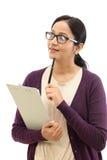 Jeune femme pensant tout en prenant des notes photo stock