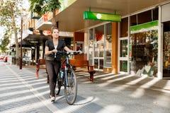 Jeune femme permutant sur la bicyclette photographie stock libre de droits
