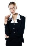 Jeune femme perplexe d'isolement d'affaires avec un crayon lecteur Images stock