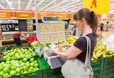 Jeune femme pesant des bananes sur les échelles électroniques dans le département de produit Image stock