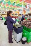 Jeune femme pesant des légumes sur les échelles électroniques Image stock